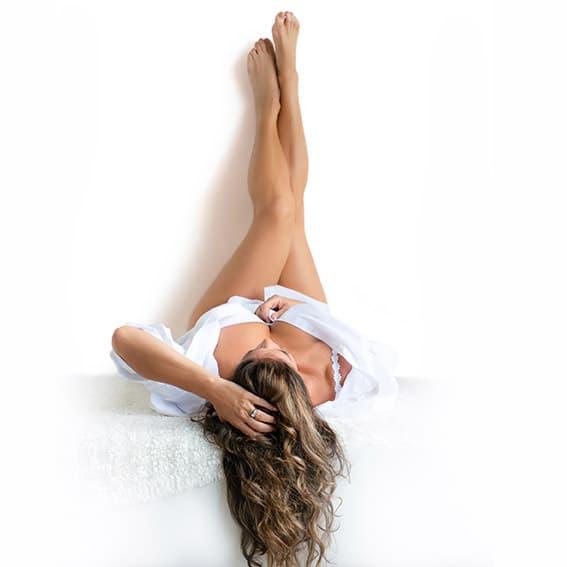 Boudoir witte overhemd pose hand in haar benen omhoog wegkijken