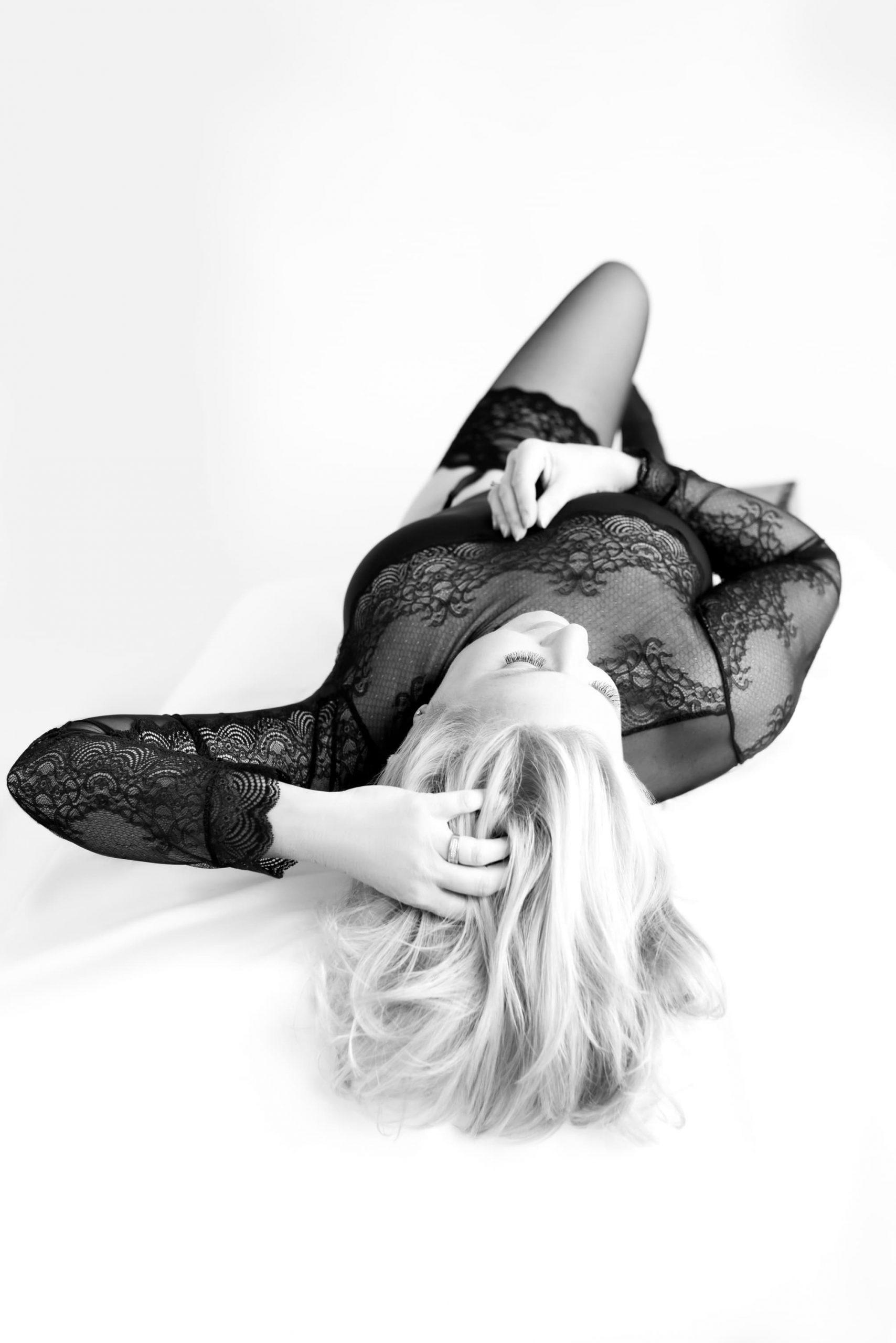 Boudoir dame in zwarte body pose hand in haar liggend