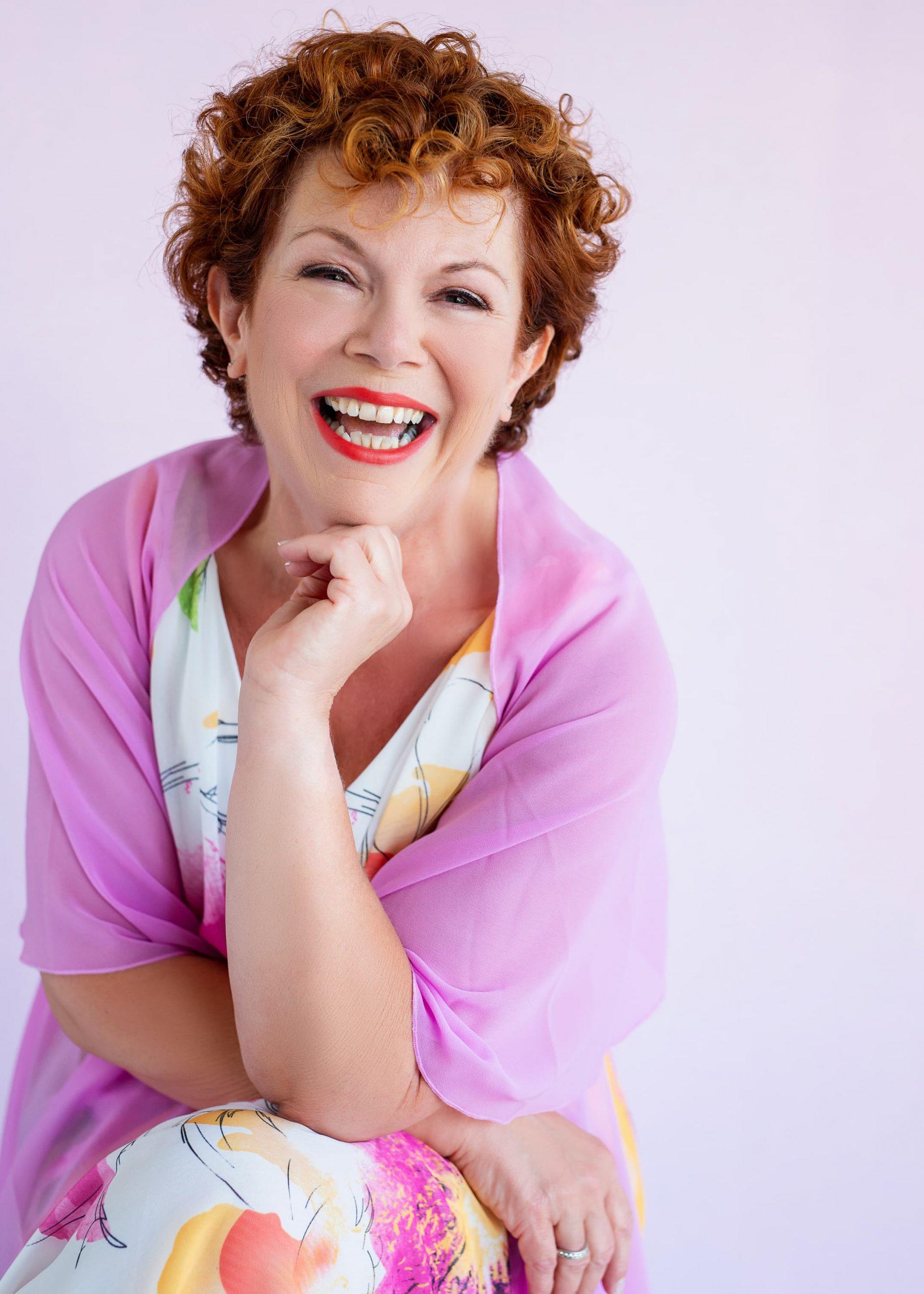vrolijke vrouw met roze sjaal rode lippenstift en korte rode krullen