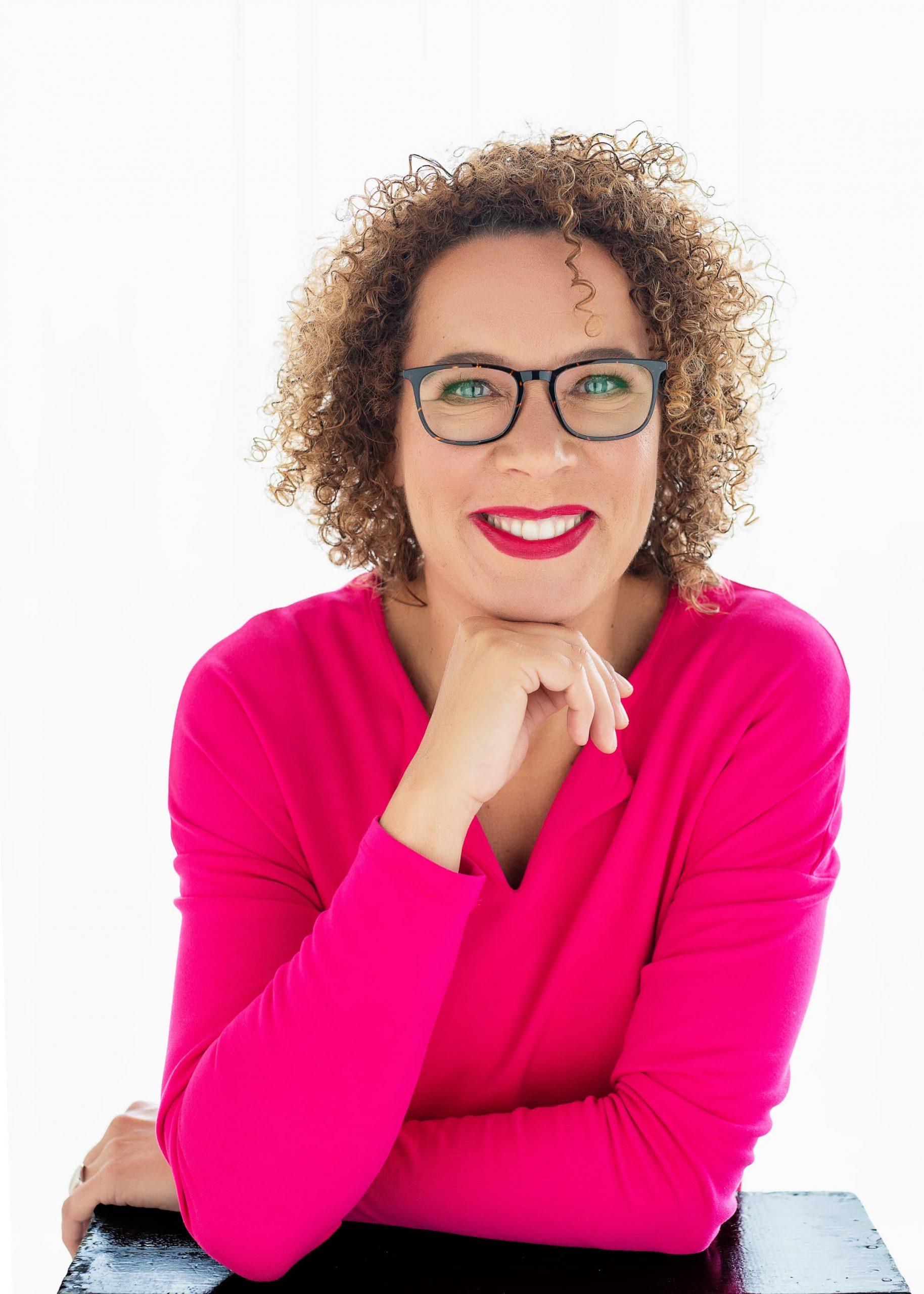 vrouw in roze trui met roze lippenstift en bril